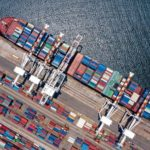Container_ship_loading_and_unloading_in_deep_sea_port,_Aerial_view_of_business_logistic_import_and_export_freight_transportation_by_container_ship_in_open_sea,_Container_loading_Cargo_freight_ship.