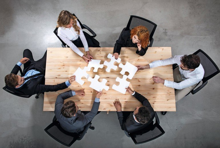 Businessmen_working_together_to_build_a_puzzle._Concept_of_teamwork,_partnership,_integration_and_startup.