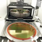 Silicon_wafers_on_machine,_detail_of_a_silicon_wafer_reflecting_different_colors.blurred_background