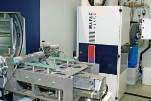 Die_Produktionslinie_bei_der_Firma_ALPLA_ist,_einschließlich_der_Reinigung,_vollautomatisiert._Die_Reinigungsmaschine_MAFAC_PALMA_wird_von_einem_Knickarmroboter_bestückt.